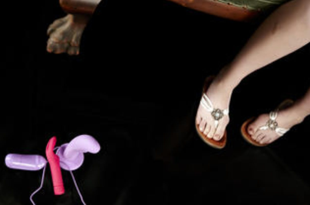 Image of three sex toys laying at someone's feet.