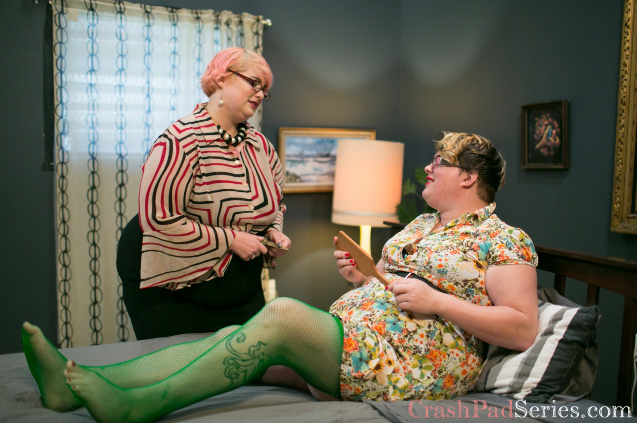 Photo of Jetta Rae laying on a bed holding a paddle while Kitty Styker stands next to her in conversation.