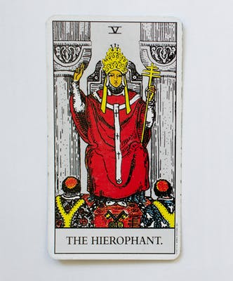 The Hierophant tarot card. Image of a person sitting in a throne between two pillars wearing a crown and red cape, with both hands raised one holding a scepter.