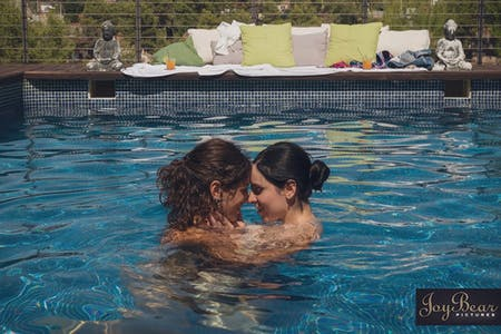 two female performers share a kiss in the pool