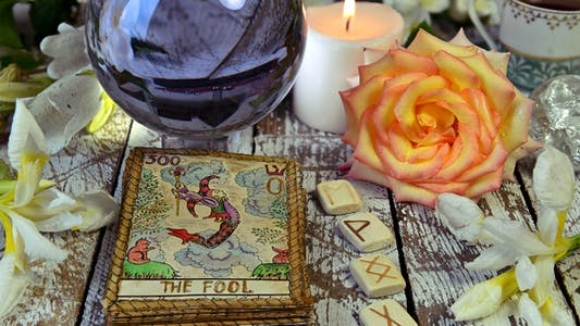 psychic love reading table featuring The Fool tarot card, a rose, and runes