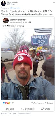 """""""Yes, I'm friends with him on FB. He goes HARD for Trump. Totally uneducated based on his grammar."""" Photograph of Jason Alexander wearing a red ad white '45' bobble hat and a jean jacket, taken at the Capitol Hill riots with flag waving rioters behind him"""