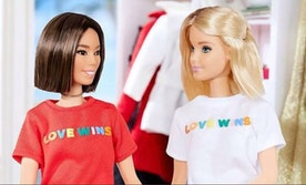 An Asian doll with a brown bob wearing a red love wins t-shirt sits across from Barbie who is wearing a matching white t shirt