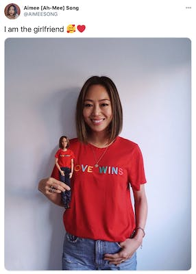 """""""I am the girlfriend 🥰❤️"""" A photograph of the blogger, an Asian woman with short brown hair wearing a red love wins t-shirt, smiling and holding the doll based off her whose wearing a matching outfit"""
