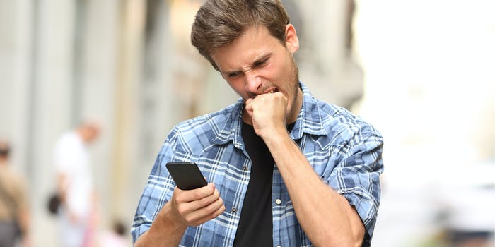 man biting fist while looking at phone