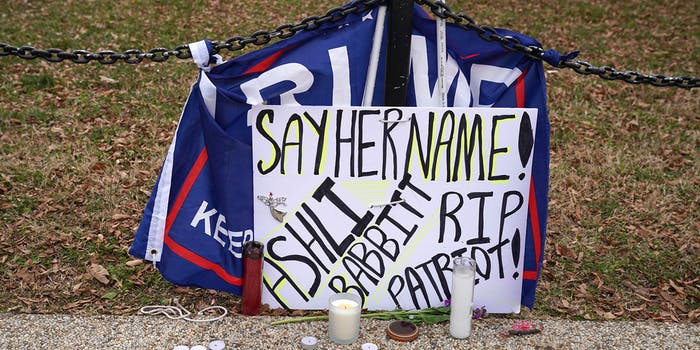 "hand-written poster reading ""Say her name! Ashli Babbitt RIP Patriot!"" with Trump flag and candles"