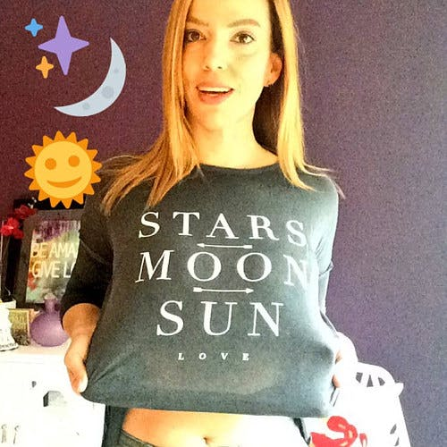 "Picture of Danielle smiling with her shirt that's branded the same as her astrology services. The shirt reads ""Stars, moon, sun, and love"""