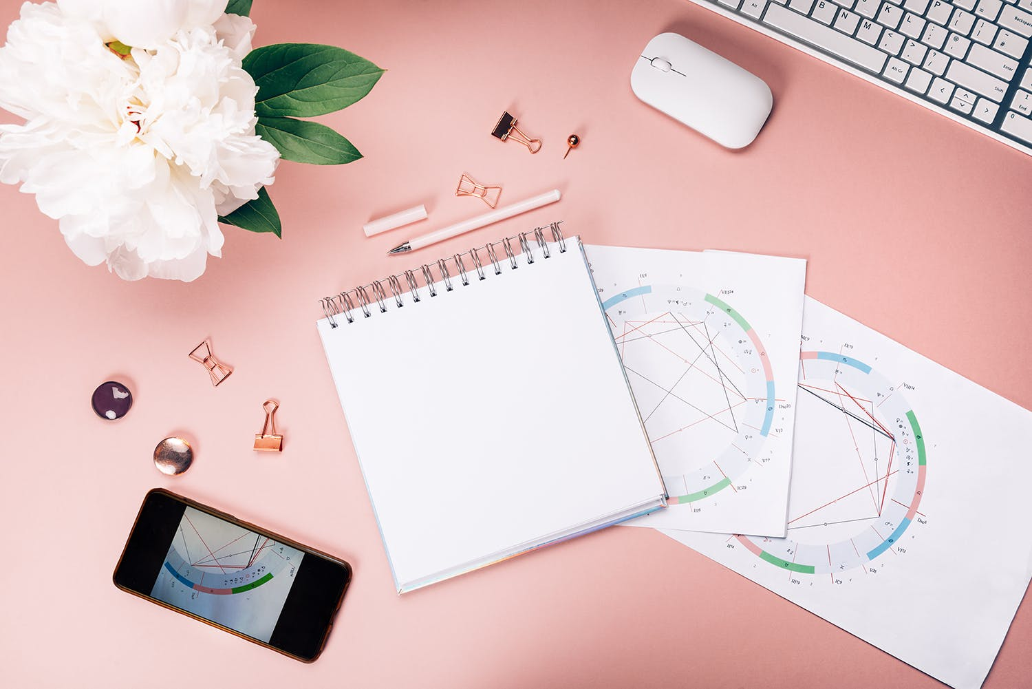 Photo of a cellphone, notebook, hand drawn birth charts, and a computer with a bouquet of flowers next to it on a pink background.