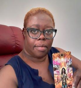 Image of Ms. Adriene (A.D) Joyce holding a tarot card.