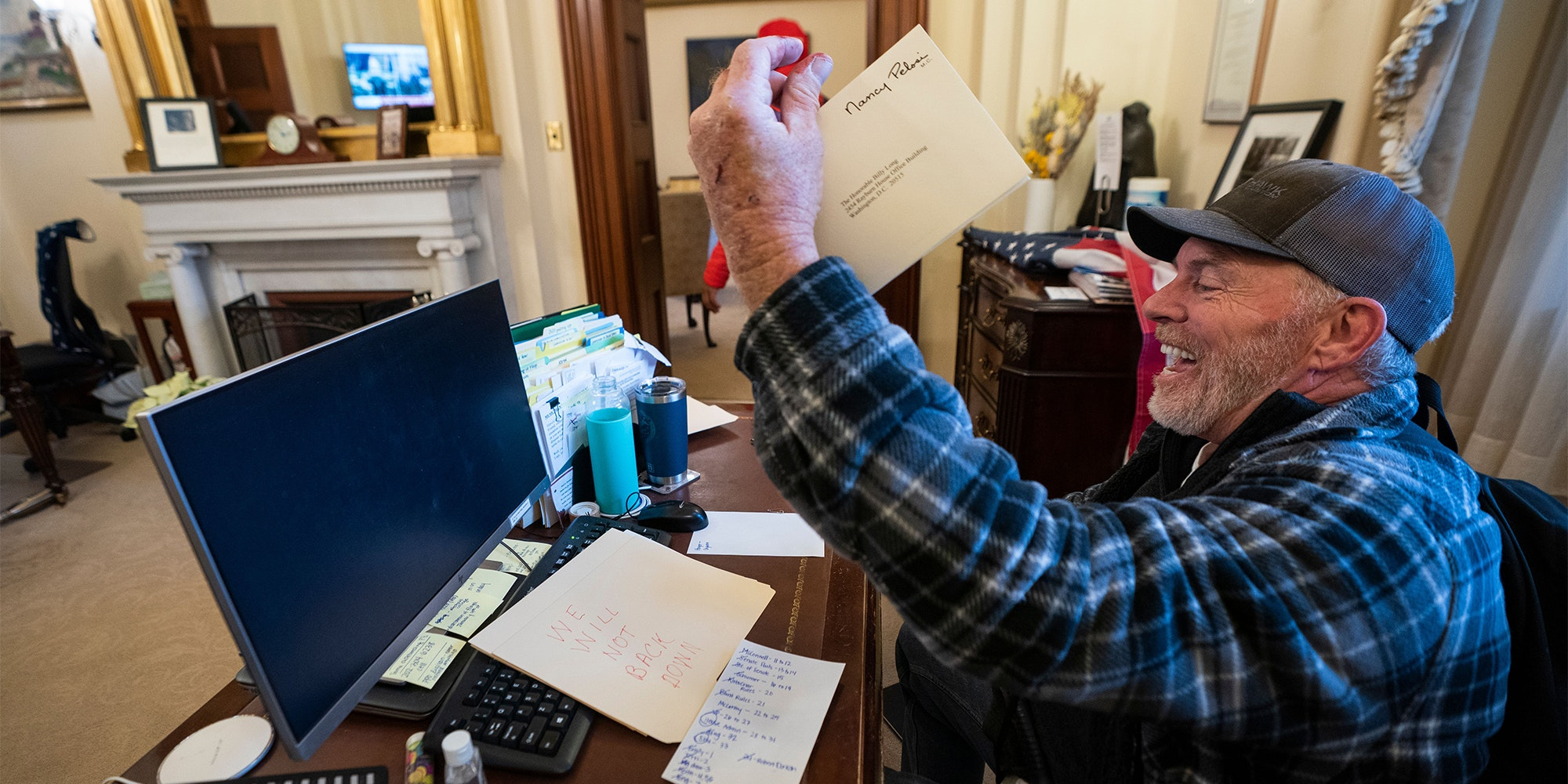 """""""Bigo"""" Barnett holds a piece of Nancy Pelosi's mail in the air, laughing as he sits at her desk"""