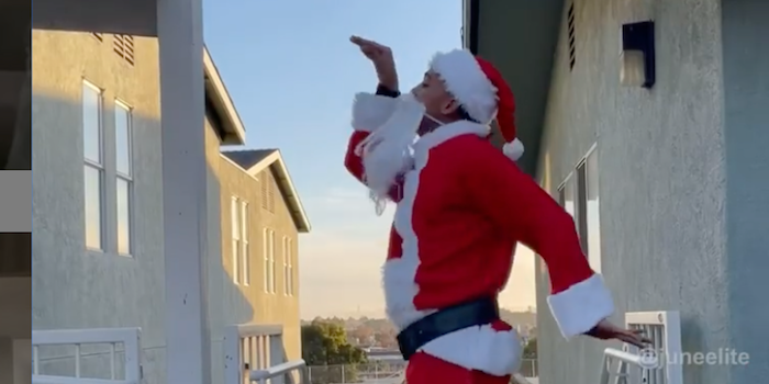 A Black man in a Santa suit and beard does the Junebug Challenge dance in an alley between houses