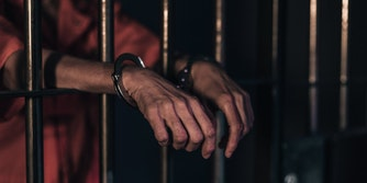 A person in handcuffs behind bars