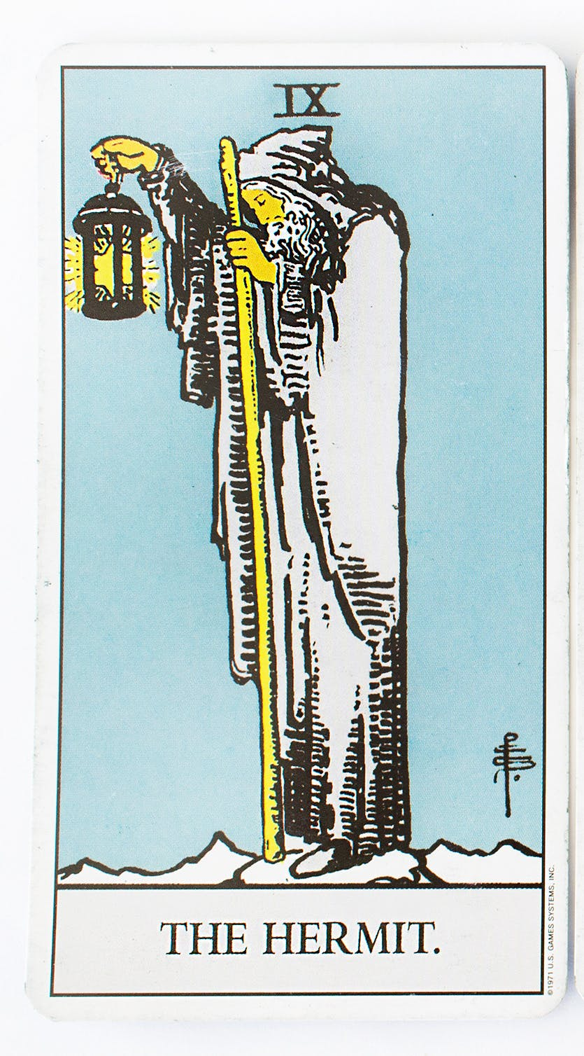 The Hermit in the Ride-Waite deck. Features an image of a man dressed in white holding a walking stick in one hand and a latern in the other.