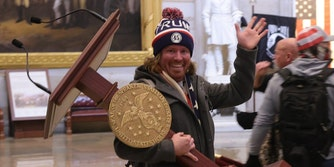 man in Trump 45 hat waving and smiling as he steals the lectern from the House of Representatives. Some people online thought his name was actually 'Via Getty.'