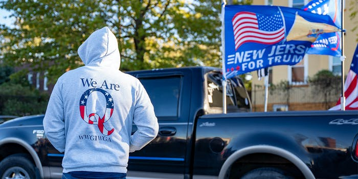 """person wearing """"We Are Q WWG1WGA"""" hooded sweatshirt in front of truck with New Jersy For Trump flag"""