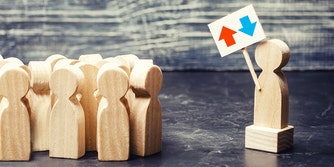 wooden figure on platform holding reddit upvote/downvote icon sign, in front of crowd of other wooden figures
