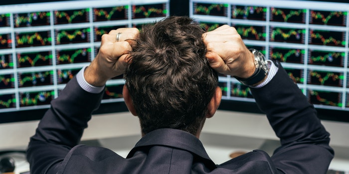 Stock trader tearing out his hair from despair, rear view