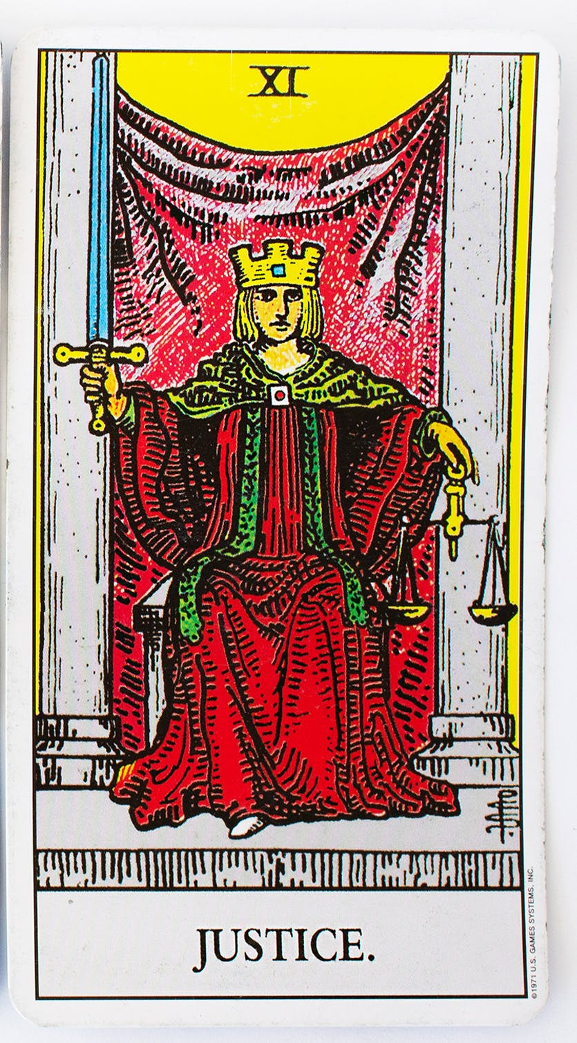 The justice card from the rider-waite deck. Features an image of a person sitting in a throne wearing a red robe and a crown, holding a set of scales in one hand and a sword in the other.