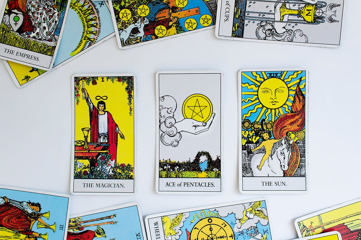 Photo of the Rider-Waite tarot deck spread out, with the magician, ace of pentacles, and the sun facing out.