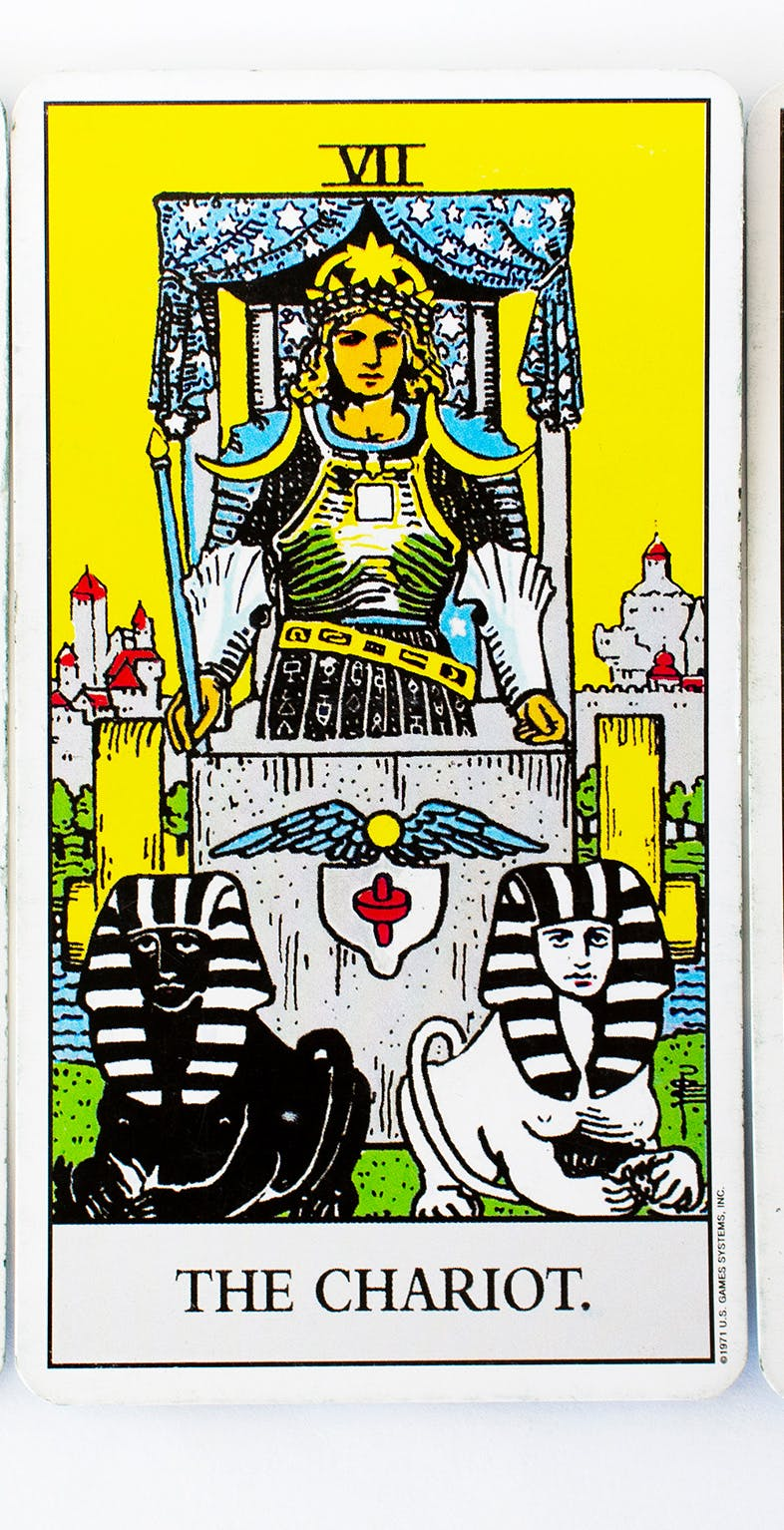 The Chariot card in the Rider-waite tarot deck. Image of shows a brave warrior standing inside a chariot. He wears armour decorated with crescent moons and has two lions at his feet.