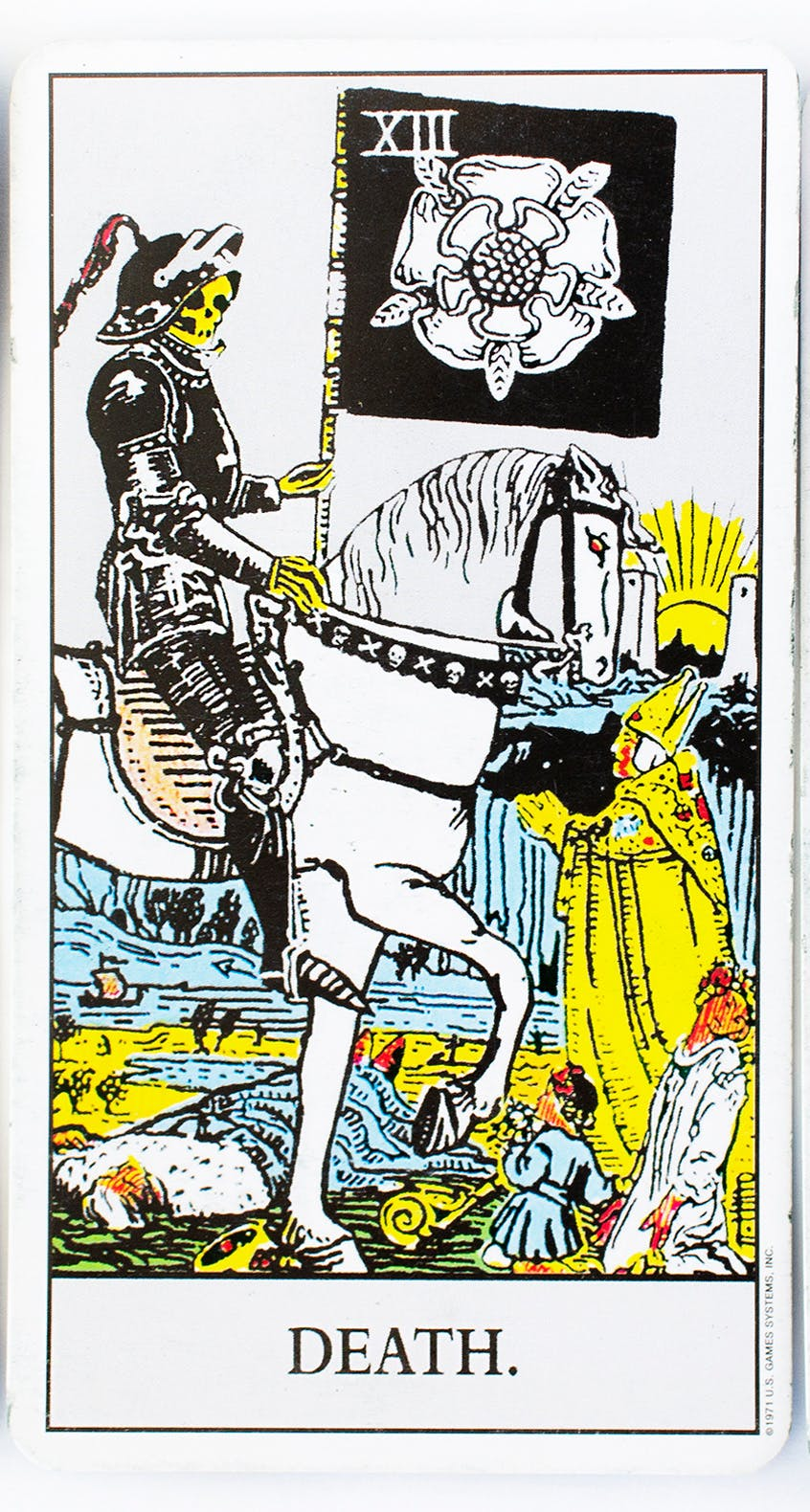 teh death tarot card from the rider-waite deck. image of a skeleton riding a horse while holding a sickle and common people being crushed underneath.
