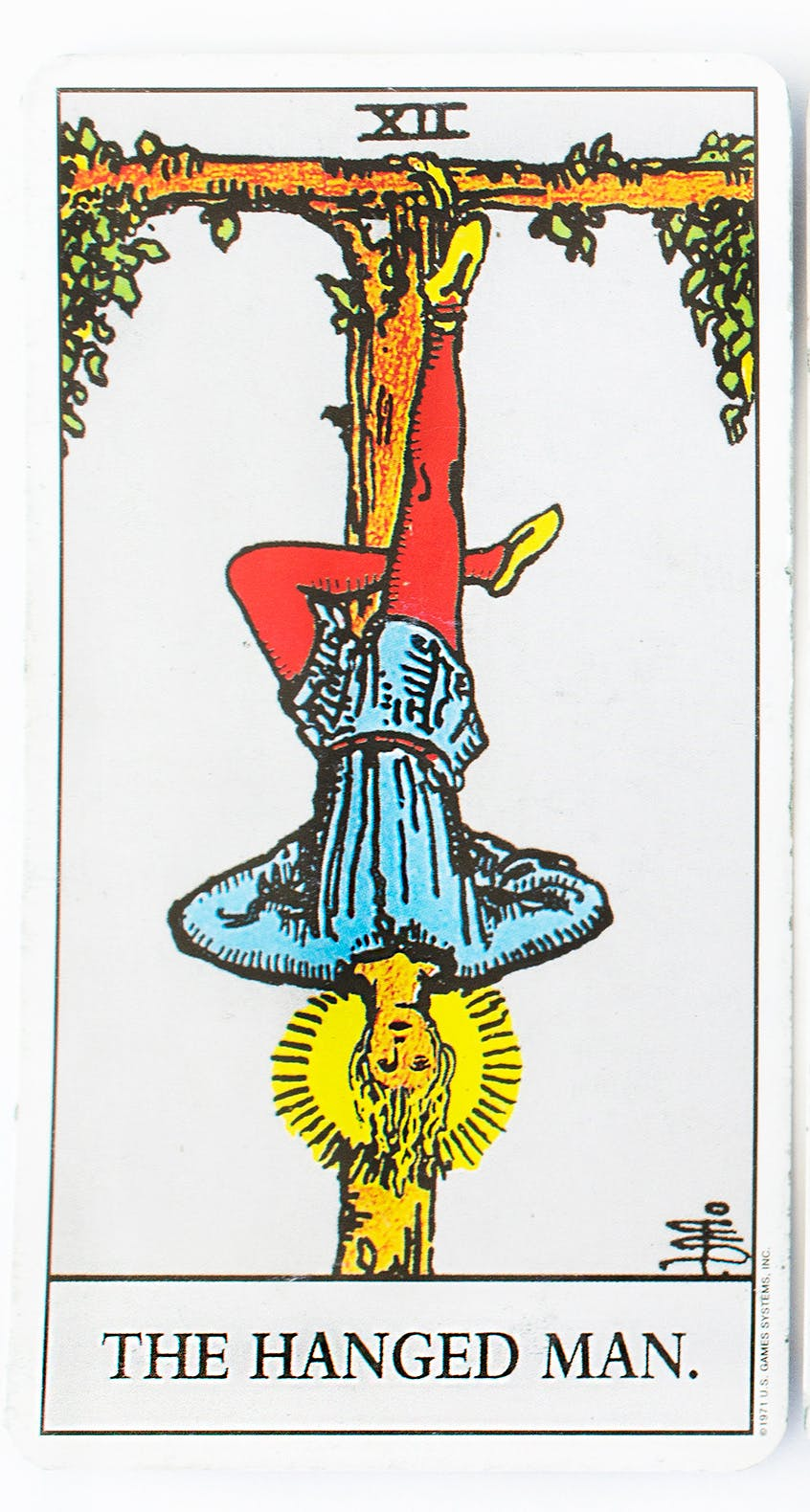 the hanged man from the Rider-Waite tarot deck. image of a man hanging by one ankle upside down on a cross.