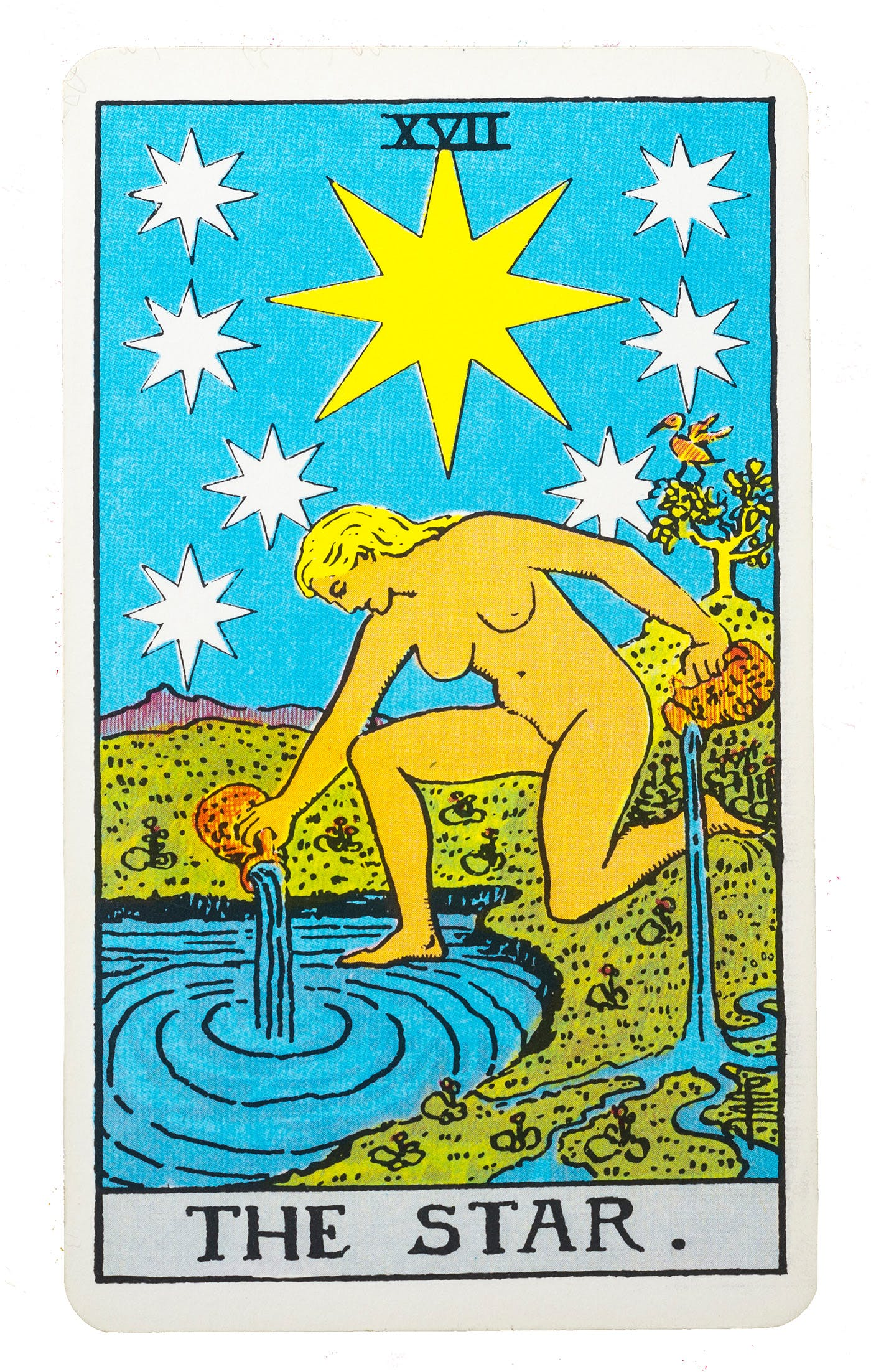 The Star tarot card from the rider-waite deck. Image of a woman kneeling by a lake pouring cups of water into the lake.