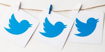twitter logos on cardboard, hanging from a string