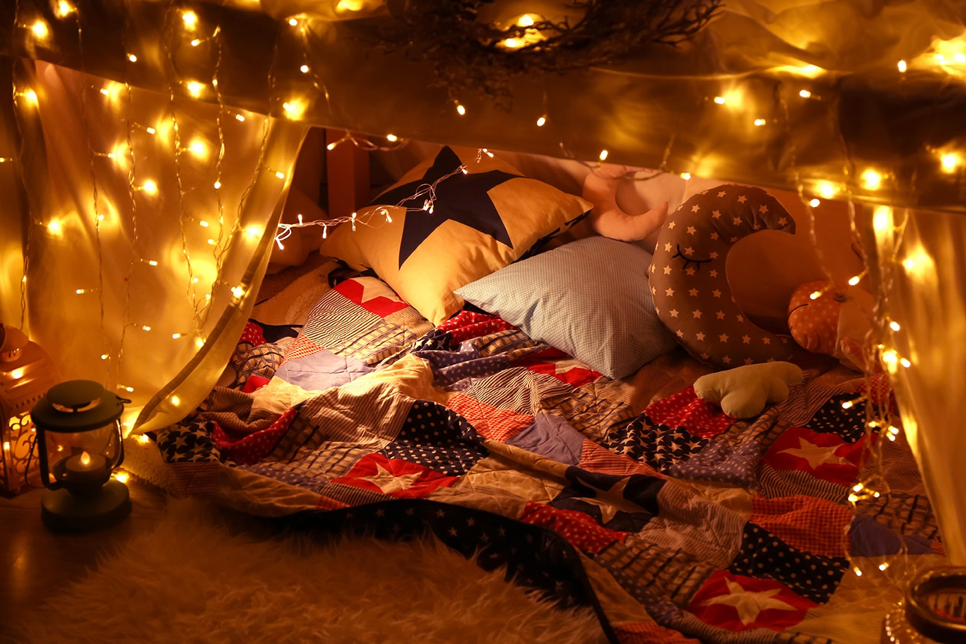 Blanket fort decorated with pillows and string lights.