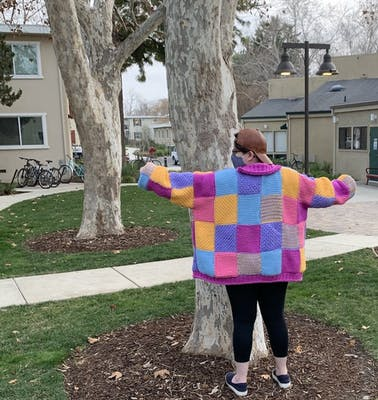 An image of a person showing off their homemade Harry Styles cardigan.