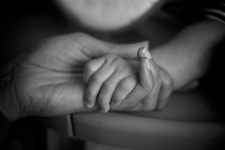 A hand of a parent holding the hand of an infant