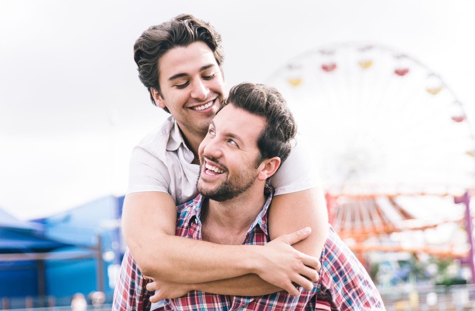 Two men embrace each other outside of a carnival