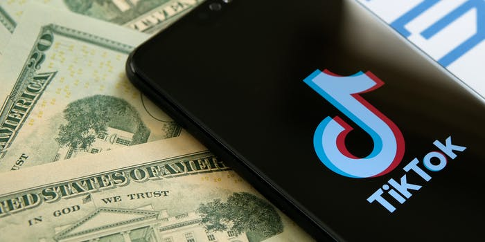 A phone showing the TikTok logo next to $20 bills.