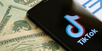 A phone showing the TikTok logo next to $20 bills.