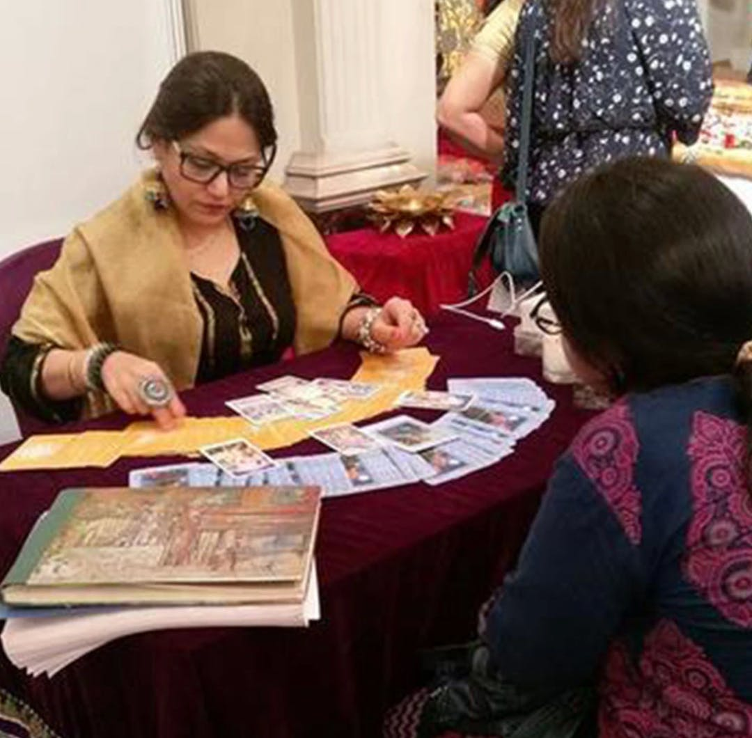 Mystic Pal Ginni uses tarot to conduct a reading for a client.