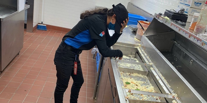 domino's worker leaning over counter with hand on head