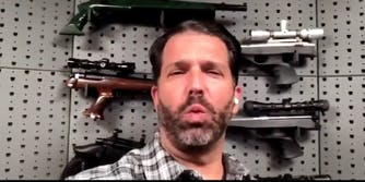 Donald Trump Jr. in front of guns