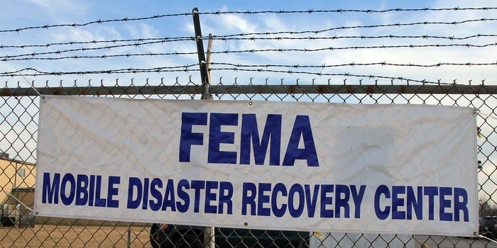 FEMA Mobile disaster recovery center sign on chainlink fence with barbed wire top