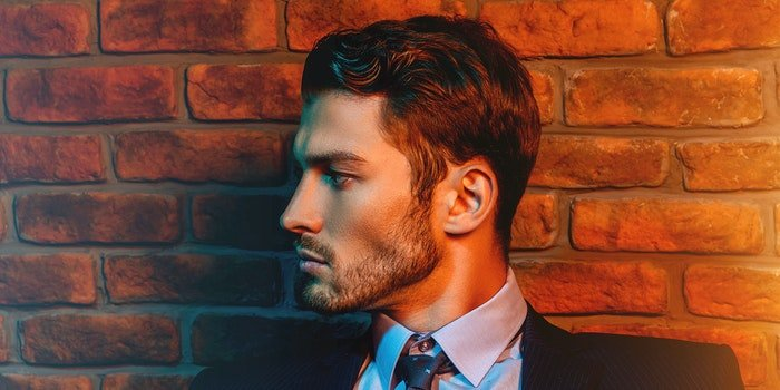 Handsome man in suit in front of brick wall.