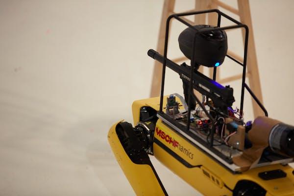 A Spot robot with a paintball gun attached