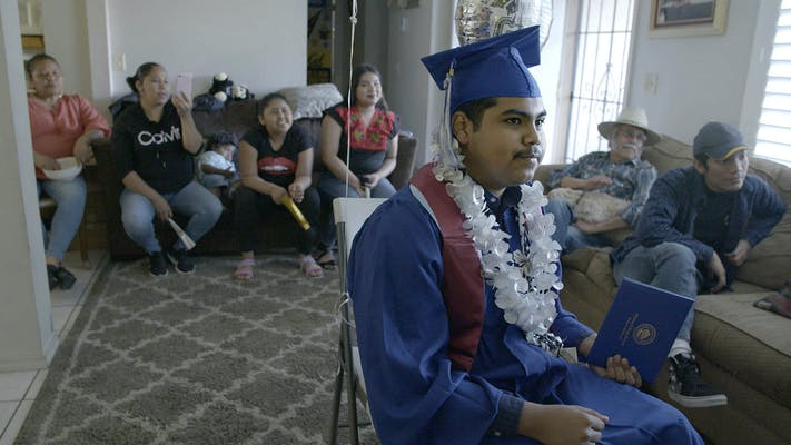 teen wears graduation gown for virtual ceremony as family looks on