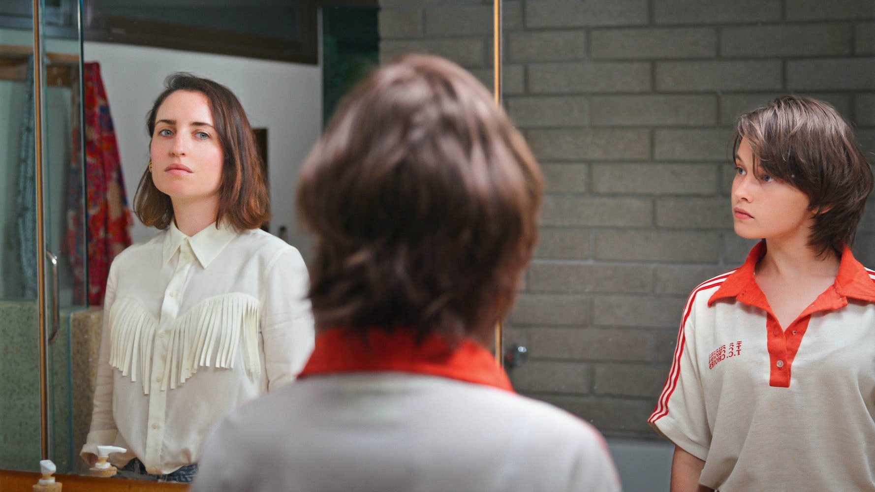 two women look at each other in front of mirror