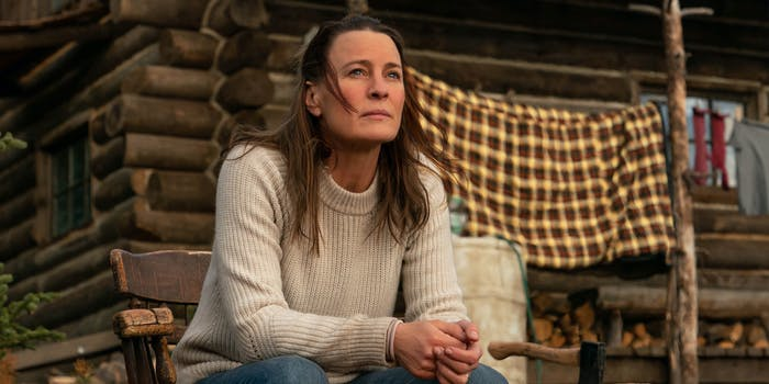 robin wright sits outside a cabin in land