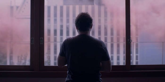 man stares at the window with pink hue
