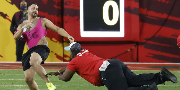 Security guard dives toward fan in pink onesie and black shorts running across the field of Super Bowl LV.