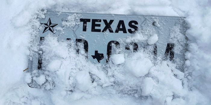 Texas license plate covered in snow