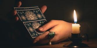 Hands shuffling a tarot deck in candlelight.