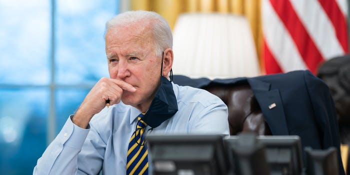 Joe Biden in the Oval Office with his hand up to his face.
