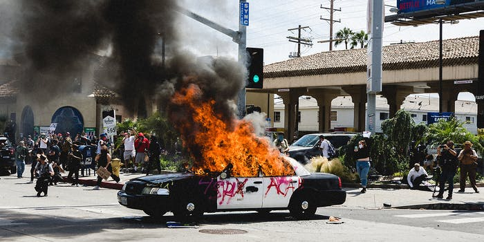 An LAPD car on fire while people watch it burn.