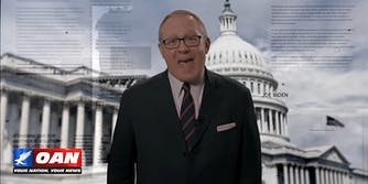 Man speaking in front of US Capitol backdrop with OAN logo